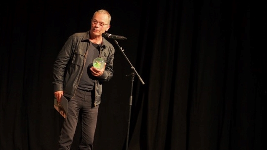 Thomas Heise steht am Mikrofon und hält den Preis (eine Schneekugel) in der rechten Hand und in der linken Hand die Urkunde