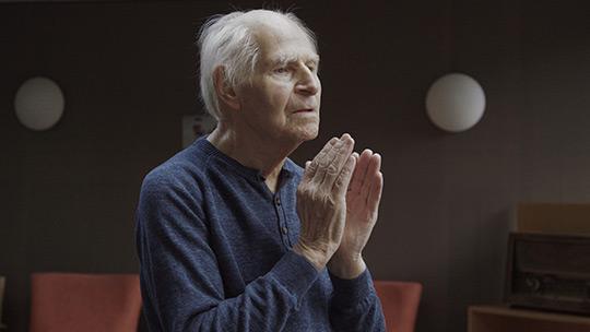 Filmstill aus dem Berlinale Beitrag das innere Leuchten. Man sieht Manfred Volz wie er mit geschlossenen Augen die Hände hochhält.