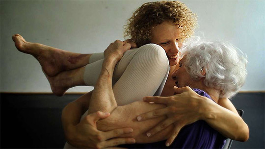 Filmstill from the documentary The Euphoria of Being. The young dancer Emese Cuhorka is carrying the over 90 years old Eva Fahidi in her arms.