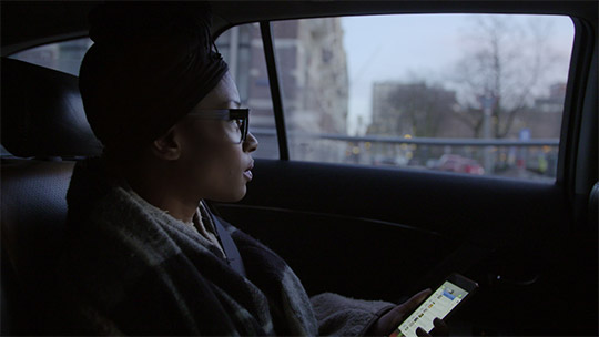 Sylvana Simon sitting in a car looking through a window. It has a touch of lonliness.