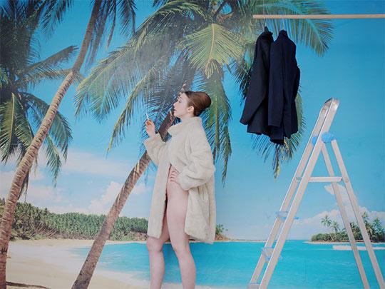 Filmstill aus dem Film 'Das melancholische Mädchen'. Die Protagonistin posiert im Profil an einer Fototapete mit Palmen, hat einen Pelzmantel an, unter dem sie nicht bekleidet ist, hält in ihrer rechten Hand eine Zigarette und spricht.