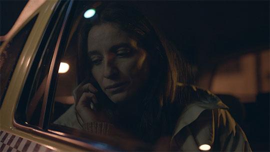 Ein Filmstill aus Monstri. Der Ausschnitt zeigt die Hauptfigur Dana gefilmt durch eine Autoscheibe, wie sie im Dunkeln telefoniert. Sie schweigt.