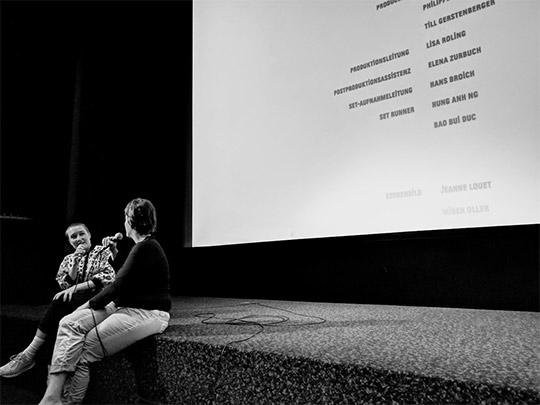 Susanne Heinrich sitzt nach der Vorstellung auf der Vorbühne und diskutiert mit einer Moderatorin von Crossing Europe über ihren Film. Das Bild ist in Schwarz-Weiss.